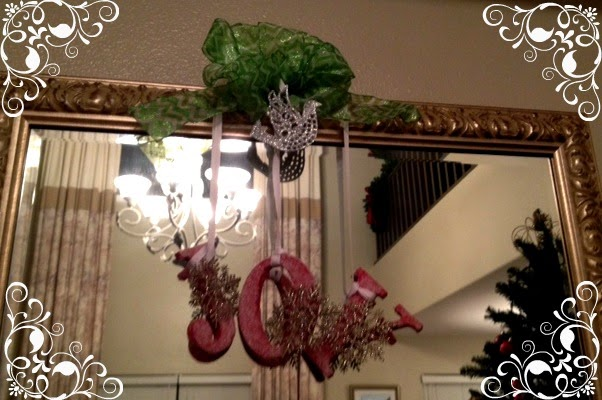 here is a simple hanging decor i made using wooden letters glittered ornaments ribbons and a wire coat hanger i hangs above the mirror in my foyer